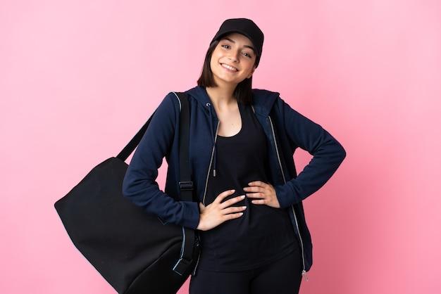 엉덩이에 팔을 포즈와 미소 핑크 벽에 고립 된 스포츠 가방 젊은 스포츠 여자