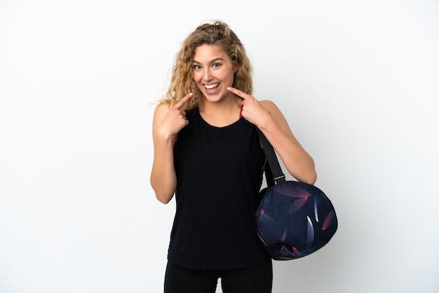 흰색 배경에 격리된 스포츠 가방을 들고 엄지손가락 제스처를 하는 젊은 스포츠 여성