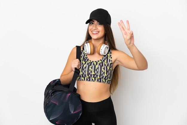 흰색 배경에 격리된 스포츠 가방을 든 젊은 스포츠 여성은 행복하고 손가락으로 세 개를 세고 있습니다.