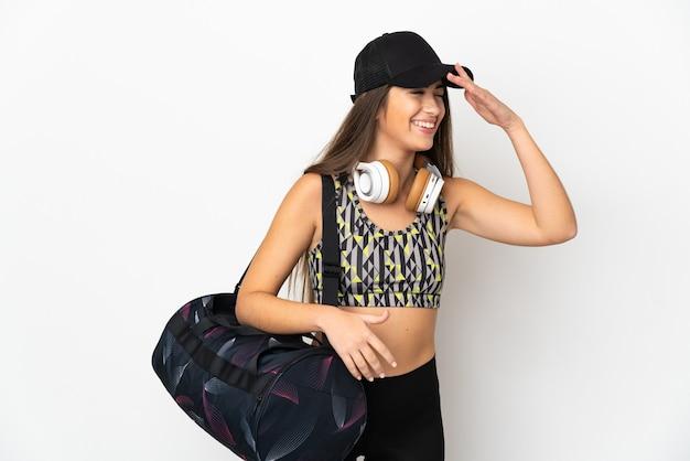 흰색 배경에 고립 된 스포츠 가방을 가진 젊은 스포츠 여자는 뭔가를 실현하고 해결책을 계획하고 있습니다