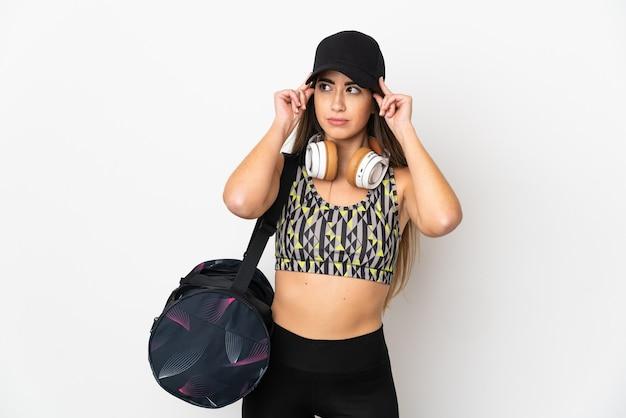 의심과 생각을 갖는 흰색 배경에 고립 된 스포츠 가방 젊은 스포츠 여자