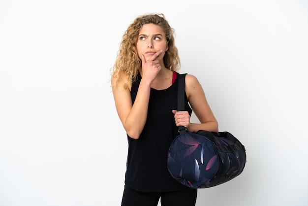 疑いを持っている白い背景で隔離のスポーツバッグを持つ若いスポーツ女性