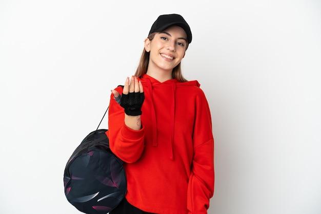 젊은 스포츠 여자 손으로와 서 초대 흰색 배경에 고립 된 스포츠 가방. 와줘서 행복해