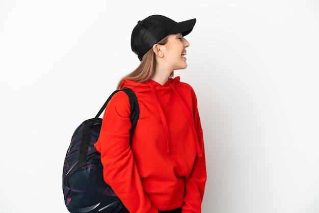 Молодая спортивная женщина со спортивной сумкой на белом фоне смеется в боковом положении