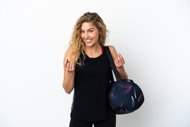 Молодая спортивная женщина со спортивной сумкой на белом фоне делает денежный жест