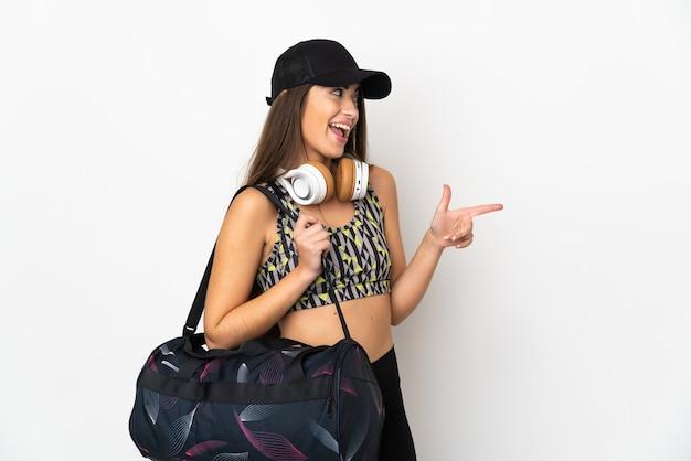 측면에 손가락을 가리키고 제품을 제시하는 흰색 배경에 고립 된 스포츠 가방 젊은 스포츠 여자