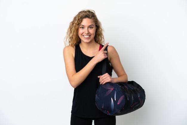 제품을 제시하는 측면을 가리키는 흰색 배경에 고립 된 스포츠 가방 젊은 스포츠 여자