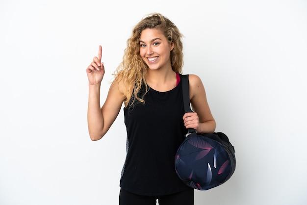 좋은 아이디어를 가리키는 흰색 배경에 고립 된 스포츠 가방 젊은 스포츠 여자