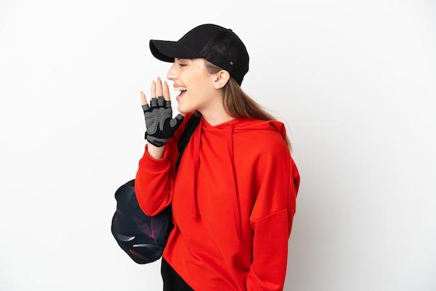 입 벌리고 측면으로 외치는 흰색 배경에 고립 된 스포츠 가방 젊은 스포츠 여자