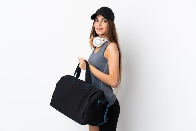 스포츠 가방을 많이 웃 고 흰색 배경에 고립 된 젊은 스포츠 여자