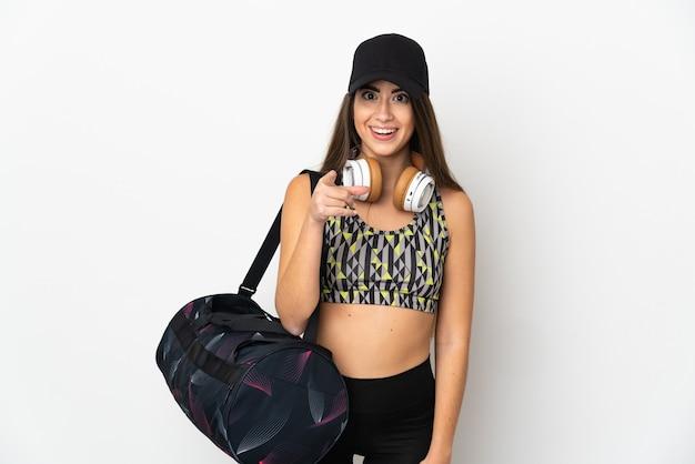 젊은 스포츠 여자 스포츠 가방 놀라게 하 고 앞을 가리키는 흰색 배경에 고립
