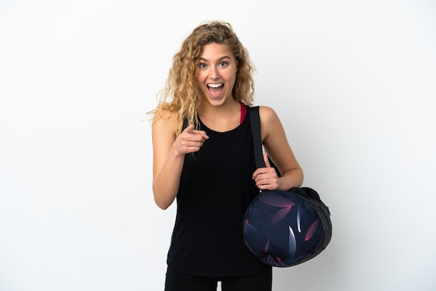 흰색 배경에 격리된 스포츠 가방을 들고 놀란 젊은 스포츠 여성