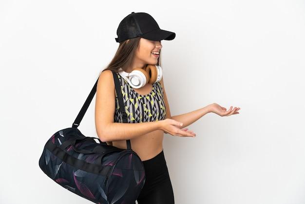 측면을 보면서 놀라운 표정으로 흰색 배경에 고립 된 스포츠 가방 젊은 스포츠 여자