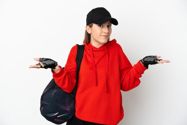 손을 올리는 동안 의심을 갖는 흰색에 고립 된 스포츠 가방 젊은 스포츠 여자