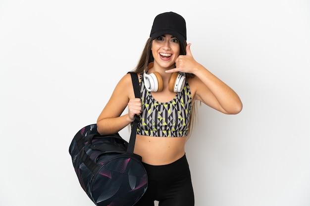 Молодая спортивная женщина с спортивной сумкой, изолированной на белой стене, делая телефонный жест. перезвони мне знак