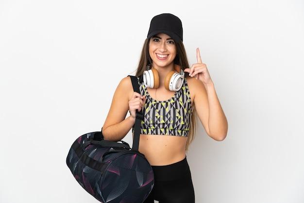 素晴らしいアイデアを指している白い壁に分離されたスポーツバッグを持つ若いスポーツ女性