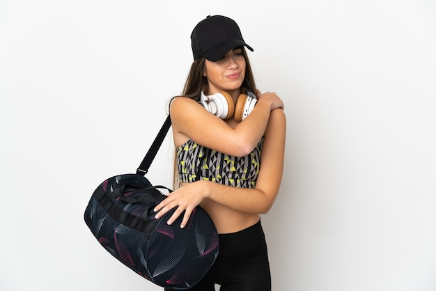 努力したために肩の痛みに苦しんでいる白い壁に隔離されたスポーツバッグを持つ若いスポーツ女性