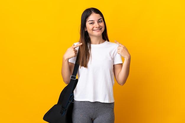 ジェスチャー親指を与える黄色に分離されたスポーツバッグを持つ若いスポーツ女性