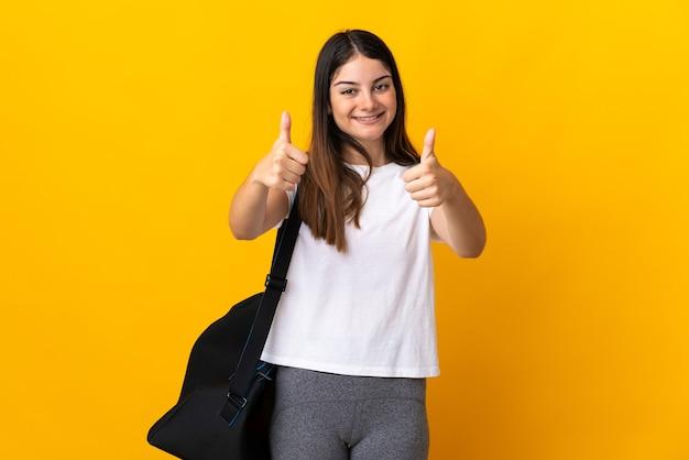 제스처를 엄지 손가락을주는 노란색에 고립 된 스포츠 가방 젊은 스포츠 여자