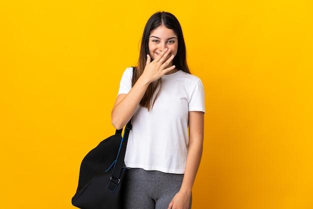 黄色の幸せと笑顔で口を手で覆うスポーツバッグで隔離の若いスポーツ女性
