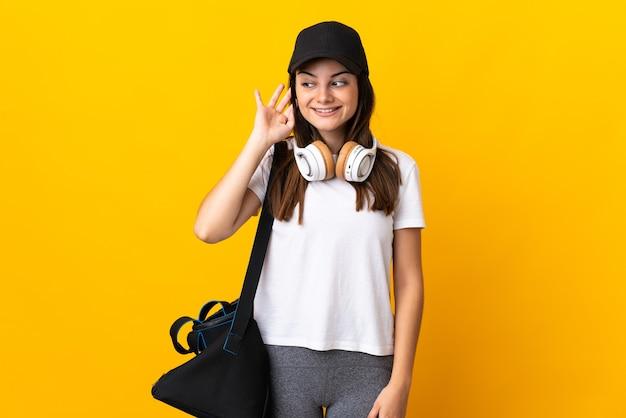 耳に手を置くことによって何かを聞いて黄色に分離されたスポーツバッグを持つ若いスポーツ女性