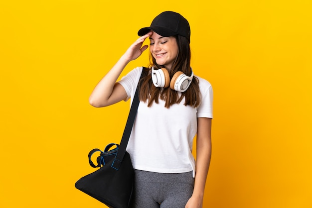 노란색 많은 미소에 고립 된 스포츠 가방을 가진 젊은 스포츠 여자