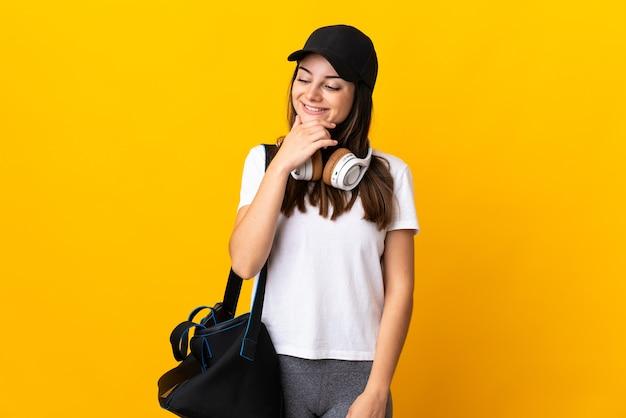横を見て笑っている黄色の壁に分離されたスポーツバッグを持つ若いスポーツ女性