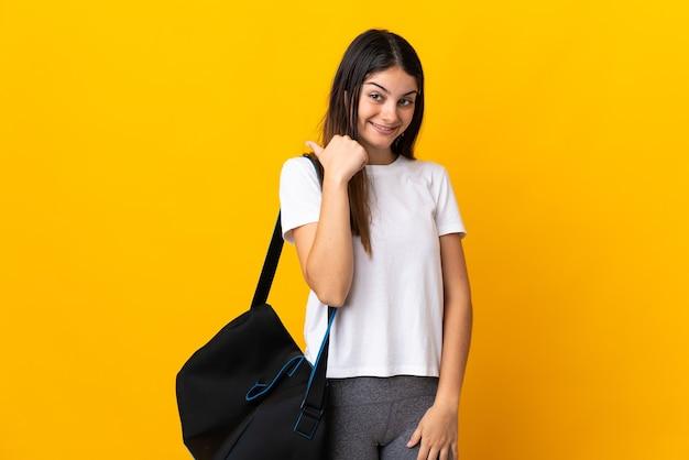 제품을 제시하기 위해 측면을 가리키는 노란색 벽에 고립 된 스포츠 가방 젊은 스포츠 여자