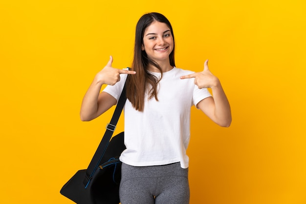 誇りと自己満足の黄色の壁に分離されたスポーツバッグを持つ若いスポーツ女性