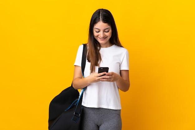 모바일로 메시지를 보내는 노란색 벽에 고립 된 스포츠 가방 젊은 스포츠 여자