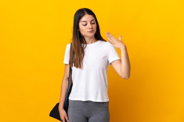 Молодая спортивная женщина со спортивной сумкой изолирована на желтой стене с усталым и больным выражением лица
