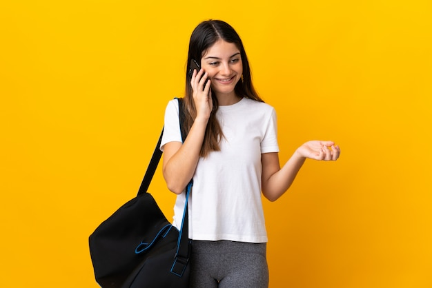 Young sport woman with sport bag isolated on yellow keeping a conversation with the mobile phone with someone