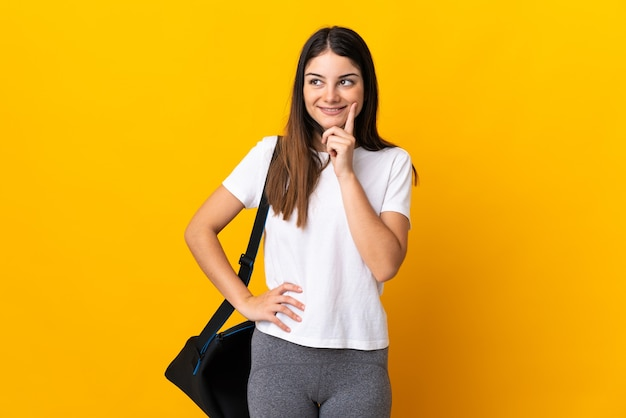 Young sport woman with sport bag isolated on yellow thinking an idea while looking up