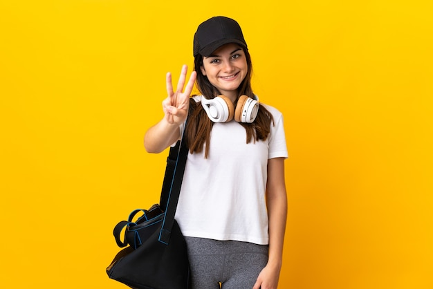 Young sport woman with sport bag isolated on yellow wall happy and counting three with fingers