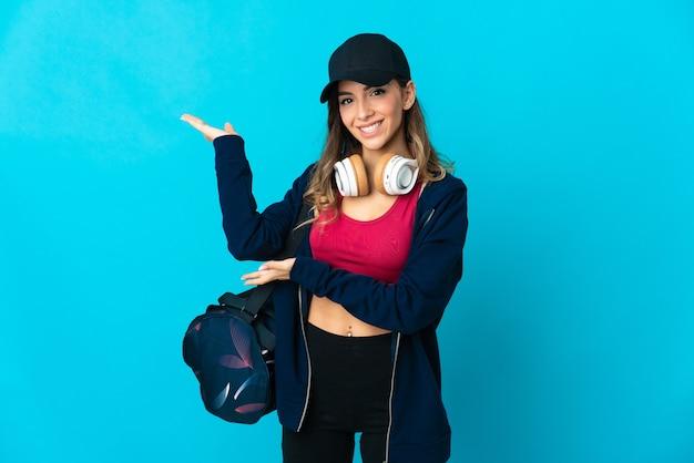 孤立したスポーツバッグを持つ若いスポーツ女性