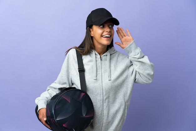 耳に手を置いて何かを聞いているスポーツバッグを持つ若いスポーツ女性