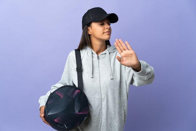 Молодая спортивная женщина со спортивной сумкой делает стоп-жест и разочарована