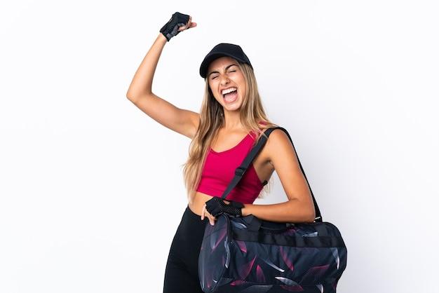 Молодая спортивная женщина со спортивной сумкой над изолированной белой стеной празднует победу