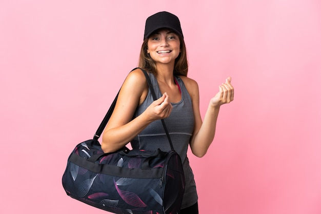 Young sport woman with sport bag on pink making money gesture