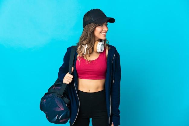Молодая спортивная женщина со спортивной сумкой позирует изолированной у глухой стены
