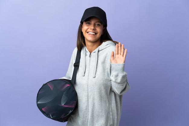 Молодая спортивная женщина со спортивной сумкой, салютуя рукой со счастливым выражением лица