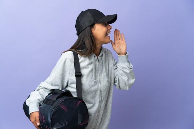 Молодая спортивная женщина со спортивной сумкой кричит с широко открытым ртом в сторону