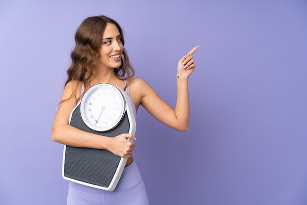 Young sport woman with weighing machine and pointing side