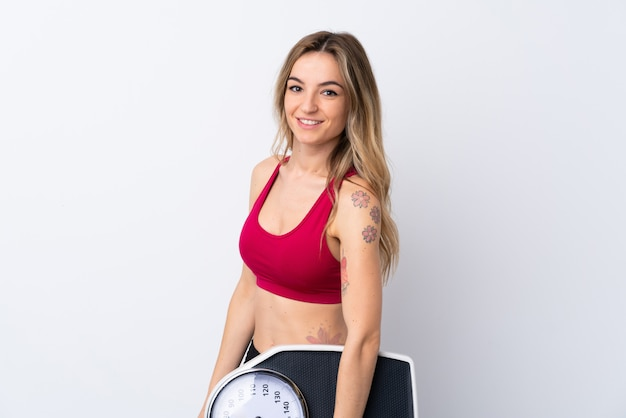 Young sport woman with weighing machine
