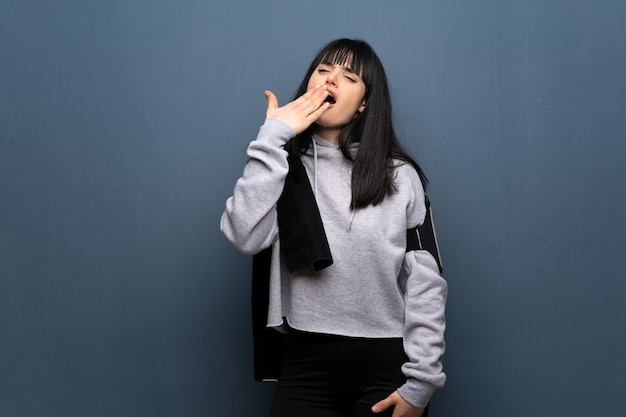 Young sport woman yawning and covering wide open mouth with hand
