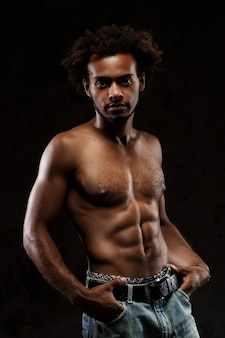 Young sportive african man posing over black wall.