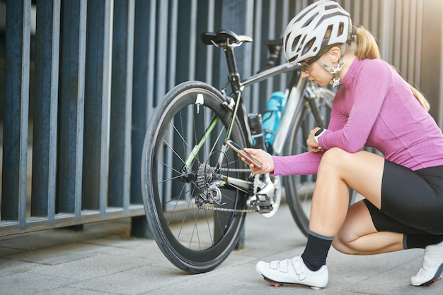 Young sportive caucasian woman female cyclist holding smartphone while checking and repairing her