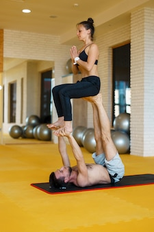 若い陽気なカップルの男の子と女の子はでヨガの練習を練習しています
