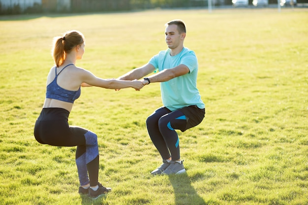 Young sportive couple doing fitness exercises on warm summer day outdoors.