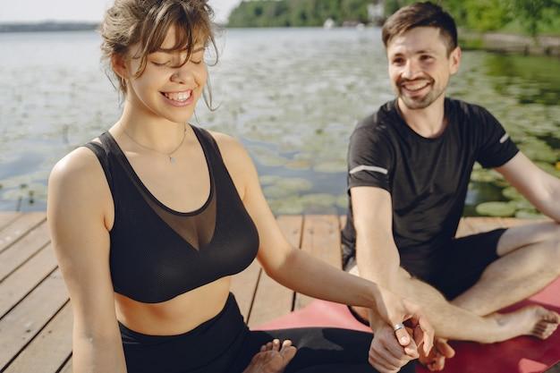 ヨガのフィットネスを行う陽気なカップル。水辺の人々。